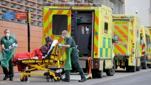 Medical staff treat an arriving patient at the Royal London Hospital in London, Monday, Jan. 11, 2021 during England's third national lockdown to curb the spread of coronavirus. The government has imposed a national lockdown while allowing schools to open, with freedom to exercise and shop for food and essential items.(AP Photo/Kirsty Wigglesworth)