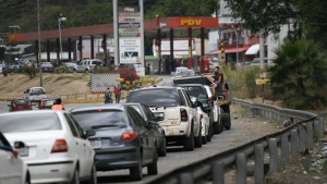 Vehicles wait in line to fill up at a gas station in the Caricuao neighborhood of Caracas, Venezuela, Tuesday, Jan. 19, 2021, amid the new coronavirus pandemic. (AP Photo/Matias Delacroix)