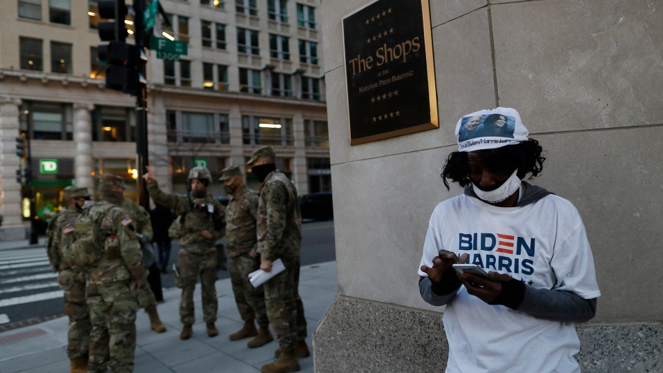 A Biden-Harris supporter stands at a corner as National Guards deploy around the city ahead of President-elect Joe Biden's inauguration ceremony, Tuesday, Jan. 19, 2021, in Washington. (AP Photo/Rebecca Blackwell)
