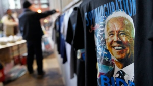 Gi Chung sets up his souvenir stand with Joe Biden memorabilia ahead of President-elect Joe Biden's inauguration ceremony, Wednesday, Jan. 20, 2021, in Washington. (AP Photo/David Goldman)