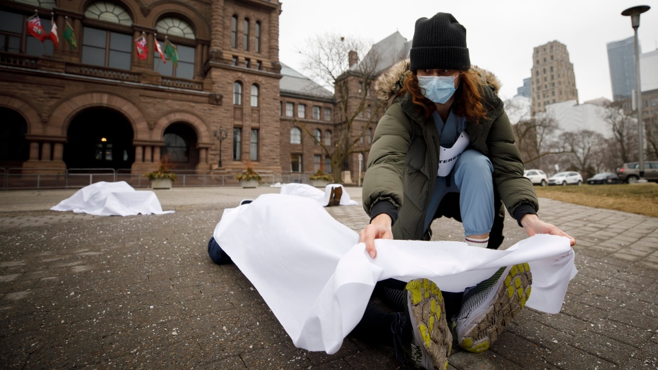 A person is covered by a sheet as a group advocating for provincially mandated paid sick days for workers participates in a 'die-in' rally outside Queens Park in Toronto, Wednesday, Jan. 13, 2021. THE CANADIAN PRESS/Cole Burston