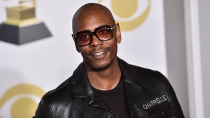 "In this Jan. 28, 2018 file photo, Dave Chappelle poses in the press room with the best comedy album award for ""The Age of Spin"" and ""Deep in the Heart of Texas"" at the 60th annual Grammy Awards in New York. (Photo by Charles Sykes/Invision/AP, File)"