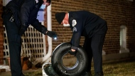 Police examine parts from an airplane wheel after it fell from a flying aircraft near several homes in the Jefferson Park neighborhood Thursday Jan. 21, 2021 in Chicago. No injuries were reported on the ground or among those on the plane, which the Chicago Department of Aviation said sent up sparks on a runway as it landed Thursday evening without its left side landing gear. (Armando L. Sanchez/Chicago Tribune via AP)
