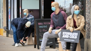 Jacob Gawrysiak puts a shoe on a mannequin as key messages are displayed in store fronts of select small business pleading for action to support local businesses during the COVID-19 pandemic in Toronto on Tuesday, December 15, 2020. THE CANADIAN PRESS/Nathan Denette