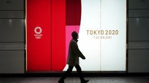 A man wearing a protective mask to help curb the spread of the coronavirus walks near a banner of the Tokyo 2020 Olympics at an underpass in Tokyo Tuesday, Jan. 19, 2021. (AP Photo/Eugene Hoshiko)
