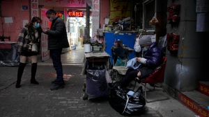 Residents wear masks as they past by a seamstress along an alleyway in Wuhan in central China's Hubei province on Friday, Jan. 22, 2021. Life appears to be back to normal on the eve of the anniversary of the 76-day lockdown in the central Chinese city where the coronavirus was first detected. (AP Photo/Ng Han Guan)