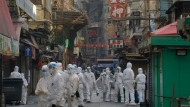 Government workers wearing personal protective equipment walk at the closed area of Jordan district in Hong Kong, Saturday, Jan. 23, 2021. Thousands of Hong Kong residents were locked down Saturday in an unprecedented move to contain a worsening outbreak in the city, authorities said. (AP Photo/Kin Cheung)