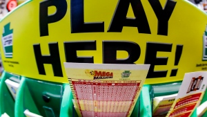 A Mega Millions playslip for those players preferring to choose the numbers they want to play is among the stacks of other lottery game playslips on display at a Smoker Friendly store, Friday, Jan. 22, 2021, in Cranberry Township, Pa. (AP Photo/Keith Srakocic)