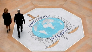 In this photo taken on Thursday, Nov.8, 2018 people walk on the Interpol logo at the international police agency headquarters in Lyon, central France. (AP Photo/Laurent Cipriani)