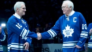 Toronto Maple Leafs alumni George Armstrong, right, and son of Maple Leafs alumni Syl Apps, Syl Apps Jr., shake hands during a pre-game ceremony before the Toronto Maple Leafs and Winnipeg Jets NHL game in Toronto on Saturday, February 21, 2015. The Toronto Maple Leafs announced that Armstrong and Apps will be added to the team's Legends Row. THE CANADIAN PRESS/Darren Calabrese