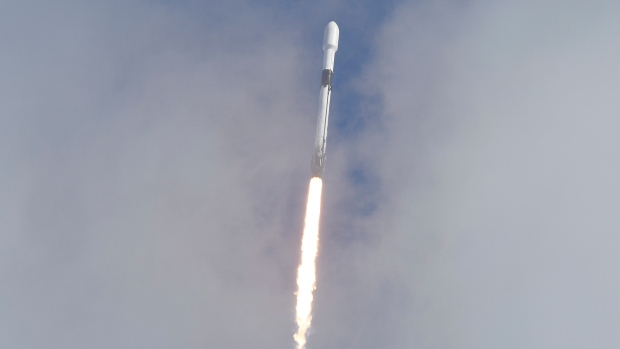 A SpaceX Falcon 9 peeks through the clouds after it lifts off on Pad 40 at Cape Canaveral Space Force Station Sunday, Jan. 24, 2021. The rocket is carrying dozens of small payloads into space on the Transporter-1 ridesharing mission. (Craig Bailey/Florida Today via AP)
