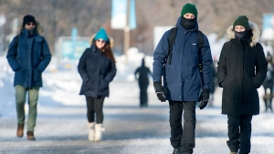 People wear face masks as they walk in the Old Port area of Montreal, Saturday, January 23, 2021, as the COVID-19 pandemic continues in Canada and around the world. THE CANADIAN PRESS/Graham Hughes