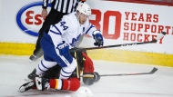 Toronto Maple Leafs' Morgan Rielly gets tangled up in the legs of Calgary Flames' Josh Leivo during first period NHL hockey action in Calgary, Sunday, Jan. 24, 2021.THE CANADIAN PRESS/Jeff McIntosh
