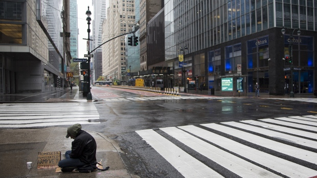 It took the world's top 1,000 billionaires nine months to recoup their fortunes after the coronavirus pandemic hit. This image shows a homeless person sitting in the rain on April 24, 2020 in New York City. (Pablo Monsalve/ViewPress/Getty Images)