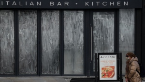 A pedestrian stops to look at the menu of a closed down restaurant in London, Saturday, Jan. 23, 2021 during England's third national lockdown since the coronavirus outbreak began. The U.K. is under an indefinite national lockdown to curb the spread of the new variant, with nonessential shops, gyms and hairdressers closed, and people being told to stay at home. (AP Photo/Kirsty Wigglesworth)