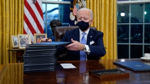 In this Jan. 20, 2021, file photo, President Joe Biden signs his first executive orders in the Oval Office of the White House in Washington. (AP Photo/Evan Vucci, File)