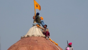 Sikhs hoist a Nishan Sahib, a Sikh religious flag, on a minaret of the historic Red Fort monument in New Delhi, India, Tuesday, Jan. 26, 2021. Tens of thousands of protesting farmers drove long lines of tractors into India's capital on Tuesday, breaking through police barricades, defying tear gas and storming the historic Red Fort as the nation celebrated Republic Day. (AP Photo/Dinesh Joshi)