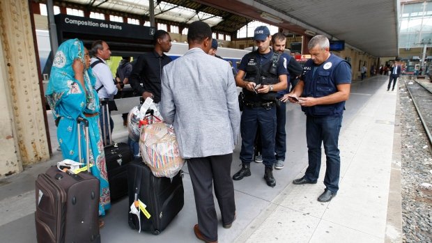 "FILE - In this Sept.15, 2015 file photo, police officers check identity documents at the Saint-Charles train station, in Marseille, southern France. In a first for France, six nongovernmental organizations launched a class-action lawsuit Wednesday, Jan. 27, 2021 against the French government for alleged systemic discrimination by police officers carrying out identity checks. Capitolin, called it a ""mechanical reflex"" for French police to stop non-whites, a practice he said is damaging to the person being checked and ultimately to relations between officers and the members of the public they are expected to protect. (AP Photo/Claude Paris, File)"