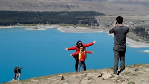 In this Oct. 6, 2018 file photo, tourists pose for a photo at the Mount John Observatory over looking Lake Tekapo, New Zealand. (AP Photo/Mark Baker,File)