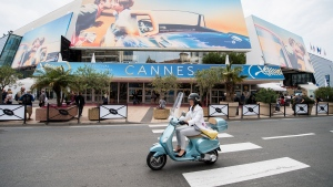 FILE - A scooter drives by the Palais des Festivals at the 71st international film festival, Cannes, southern France, on May 7, 2018. The Cannes Film Festival, canceled altogether last year by the pandemic, is postponing this year's edition from May to July in hopes of having an in-person festival. Cannes organizers announced Wednesday that this year's Cannes will now take place July 6-17, about two months after its typical period. (Photo by Arthur Mola/Invision/AP, File)