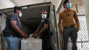 Sri Lankan health services workers unload a consignment of Oxford-AstraZeneca vaccine donated by the Indian government at a medical warehouse as a plain clothed police officer stands guard in Colombo, Sri Lanka, Thursday, Jan. 28, 2021. Sri Lanka's president on Thursday welcomed the first 500,000 doses of a COVID-19 vaccine from India, which has donated the shots to eight countries in the region. (AP Photo/Eranga Jayawardena)