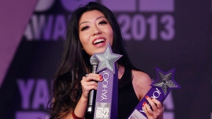 In this Dec. 1, 2013 file photo, Chinese singer-songwriter Wanting Qu holds two trophies after winning Hong Kong Most Popular Singer-Songwriter and the Best Mandarin Song at the Yahoo Buzz Awards in Hong Kong. (AP Photo/Kin Cheung, File)