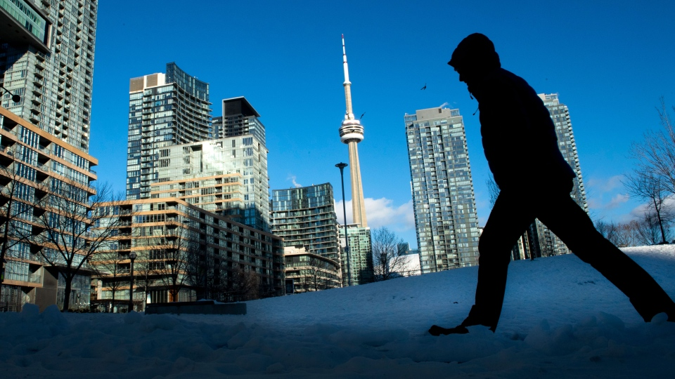 Condo towers dot the Toronto skyline as a pedestrian makes his way through the COVID-19 restricted winter landscape on Thursday January 28, 2021. CMHC says that rental vacancies are up in Canada's largest cities with rents rising too. THE CANADIAN PRESS/Frank Gunn