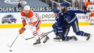 Edmonton Oilers' Connor McDavid (97) gets past Toronto Maple Leafs' Jake Muzzin (8) and Mitchell Marner (16) during second period NHL action in Edmonton on Saturday, January 30, 2021. THE CANADIAN PRESS/Jason Franson