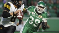 Hamilton Tiger-Cats quarterback Jeremiah Masoli, left, is chased by Saskatchewan Roughriders defensive lineman Charleston Hughes during second half CFL action at Mosaic Stadium in Regina on Thursday, July 5, 2018. THE CANADIAN PRESS/Mark Taylor