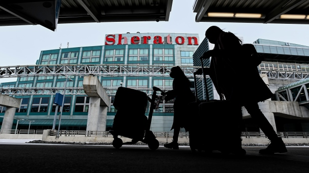 The airport hotel is shown as people walk outside with their luggage at Pearson International Airport during the COVID-19 pandemic in Toronto on Tuesday, February 2, 2021. . THE CANADIAN PRESS/Nathan Denette