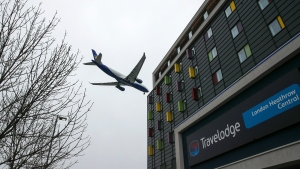 A plane passes over the Travelodge Hotel near London's Heathrow. Tuesday, Jan. 26, 2021. The U.K. is set to announce changes to its quarantine rules later Tuesday that could see anyone arriving in the country having to spend ten days in a hotel for ten days. (Steve Parsons/PA via AP)