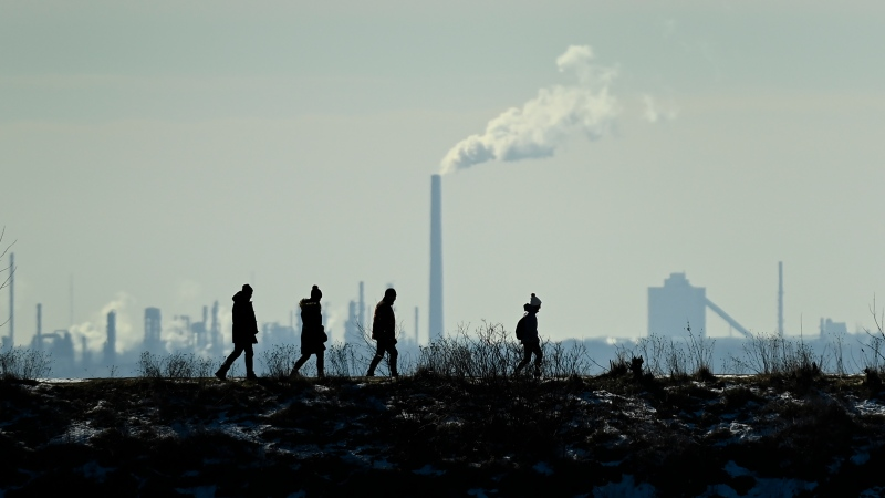 People walk along the berm on a sunny day along side lake Ontario at Colonel Samuel Smith Park during the COVID-19 pandemic in Toronto on Thursday, February 4, 2021. THE CANADIAN PRESS/Nathan Denette