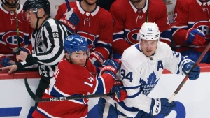 Montreal Canadiens' Nick Suzuki fends off Toronto Maple Leafs' Auston Matthews during second period NHL hockey action in Montreal on Wednesday, February 10, 2021. THE CANADIAN PRESS/Paul Chiasson