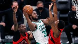 Boston Celtics' Semi Ojeleye (37) shoots against Toronto Raptors' Chris Boucher (25) and Kyle Lowry during the second half of an NBA basketball game, Thursday, Feb. 11, 2021, in Boston. (AP Photo/Michael Dwyer)