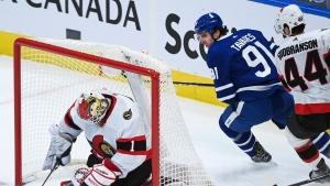 Toronto Maple Leafs centre John Tavares (91) is stopped by Ottawa Senators goaltender Marcus Hogberg (1) as Senators' Erik Gudbranson (44) defends during second period NHL hockey action in Toronto on Monday, February 15, 2021. THE CANADIAN PRESS/Nathan Denette