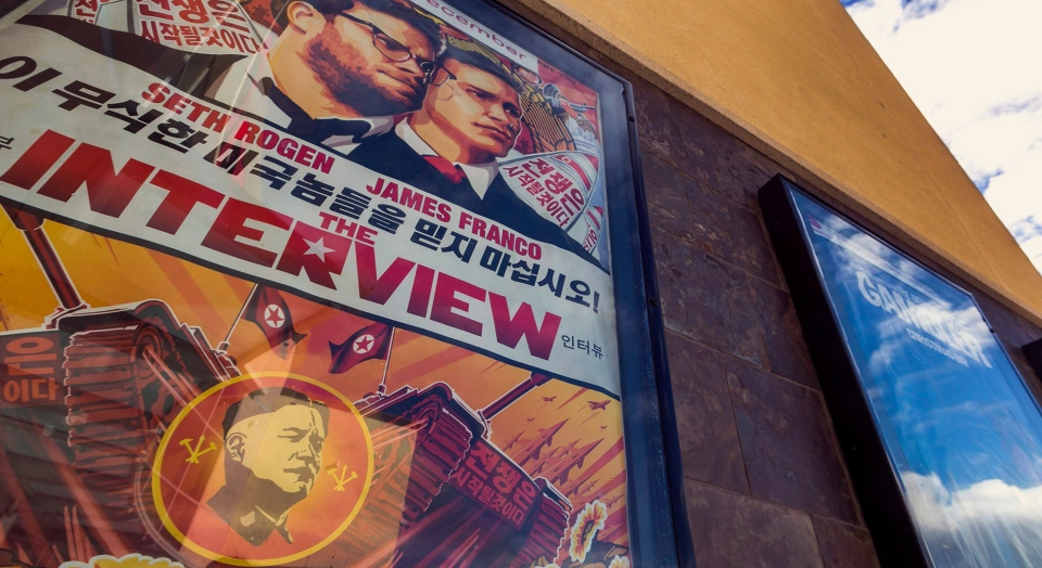 "This Dec. 17, 2014, file photo shows a movie poster for the movie ""The Interview"" on display outside the AMC Glendora 12 movie theater, in Glendora, Calif. A computer programmer working for the North Korean government was charged with devastating cyberattacks that hacked Sony Pictures Entertainment and unleashed the WannaCry ransomware virus that infected computers in 150 countries and crippled parts of the British health care system, federal prosecutors said Thursday, Sept. 6, 2018. (AP Photo/Damian Dovarganes, File)"