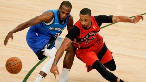 Milwaukee Bucks' Khris Middleton and Toronto Raptors' Norman Powell go after a loose ball during the first half of an NBA basketball game Thursday, Feb. 18, 2021, in Milwaukee. (AP Photo/Morry Gash)
