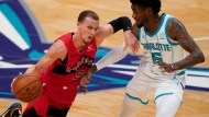 Toronto Raptors guard Malachi Flynn drives around Charlotte Hornets forward Jalen McDaniels during the first half of an NBA preseason basketball game in Charlotte, Monday, Dec. 14, 2020. (AP Photo/Chris Carlson)
