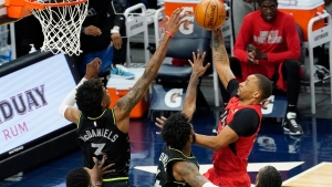 Toronto Raptors' Norman Powell, right, lays up as he is double-teamed by Minnesota Timberwolves' Jaden McDaniels (3) and Jaylen Nowell (4) in the first half of an NBA basketball game, Friday, Feb. 19, 2021, in Minneapolis. (AP Photo/Jim Mone)
