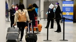 Travellers, who are not affected by new quarantine rules, arrive at Terminal 3 at Pearson Airport in Toronto early Monday, February 22, 2021. (THE CANADIAN PRESS/Frank Gunn)