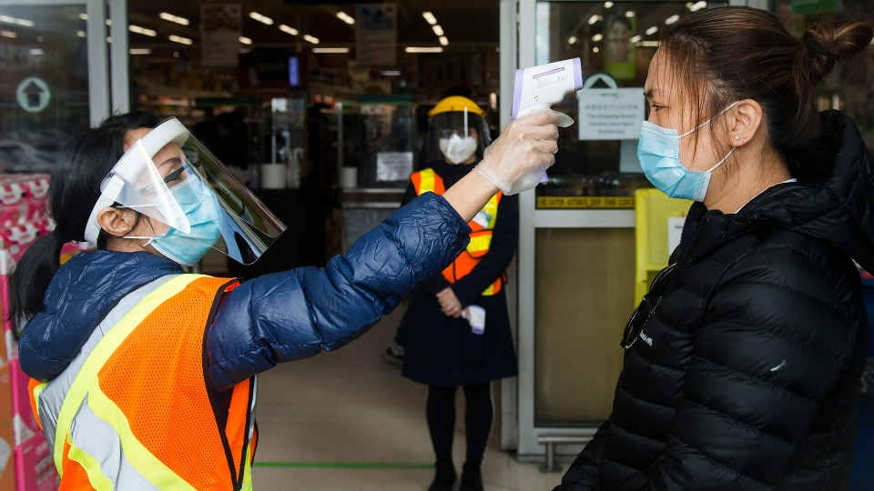FILE - People get their temperatures tested at the T&T grocery store to help curb to spread of COVID-19 in Markham, Ont., on Monday, April 20, 2020. THE CANADIAN PRESS/Nathan Denette