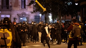 A man throws a road sign agains police officers protecting a national police station during clashes following a protest condemning the arrest of rap singer Pablo Hasél in Barcelona, Spain, Sunday, Feb. 21, 2021. Protests in support of a jailed rapper turned violent for a sixth consecutive night in Barcelona on Sunday with clashes between police and groups of mostly angry youths in the center of the Spanish city. (AP Photo/Emilio Morenatti)