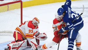 Toronto Maple Leafs centre Auston Matthews (34) gets tied up by Calgary Flames defenceman Mark Giordano (5) as Flames goaltender David Rittich (33) keeps a close eye on the loose puck during third period NHL hockey action in Toronto on Monday, February 22, 2021. THE CANADIAN PRESS/Nathan Denette