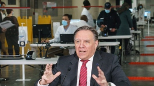 Quebec Premier Francois Legault responds to a question during a new conference in a COVID-19 vaccination clinic at Montreal's Olympic Stadium on Tuesday, February 23, 2021. THE CANADIAN PRESS/Paul Chiasson