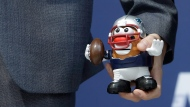Hasbro's Mexico Marketing Director Luis Martinez holds a figurine of Mr. Potato Head dressed as an NFL player, during a press conference in Mexico City, Sunday, Nov. 12, 2017. (AP Photo/Rebecca Blackwell)