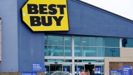 Shoppers enter and exit Best Buy store in Arlington Heights, Ill., Saturday, Feb. 6, 2021. (AP Photo/Nam Y. Huh)
