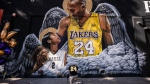 In this Jan. 26, 2021, file photo, Adam Dergazarian, bottom center, pays his respects for Kobe Bryant and his daughter, Gianna, in front of a mural painted by artist Louie Sloe Palsino in Los Angeles. Federal safety officials are expected to vote Tuesday, Feb. 9, 2021, on what likely caused the helicopter carrying Kobe Bryant, his 13-year-old daughter and seven others to crash into a Southern California hillside last year, killing all aboard. (AP Photo/Jae C. Hong, File)