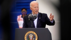 In this image taken through scaffolding, President Joe Biden speaks at a FEMA COVID-19 mass vaccination site at NRG Stadium, Friday, Feb. 26, 2021, in Houston. (AP Photo/Patrick Semansky)