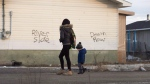 A woman and a child walk through the streets in Attawapiskat, Ont., on Monday, April 16, 2016. THE CANADIAN PRESS/Nathan Denette