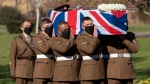 The coffin of Captain Sir Tom Moore is carried by members of the Armed Forces during his funeral, at Bedford Crematorium, in Bedford, England, Saturday, Feb. 27, 2021. Tom Moore, the 100-year-old World War II veteran who captivated the British public in the early days of the coronavirus pandemic with his fundraising efforts died, Tuesday Feb. 2, 2021. (Joe Giddens/Pool Photo via AP)